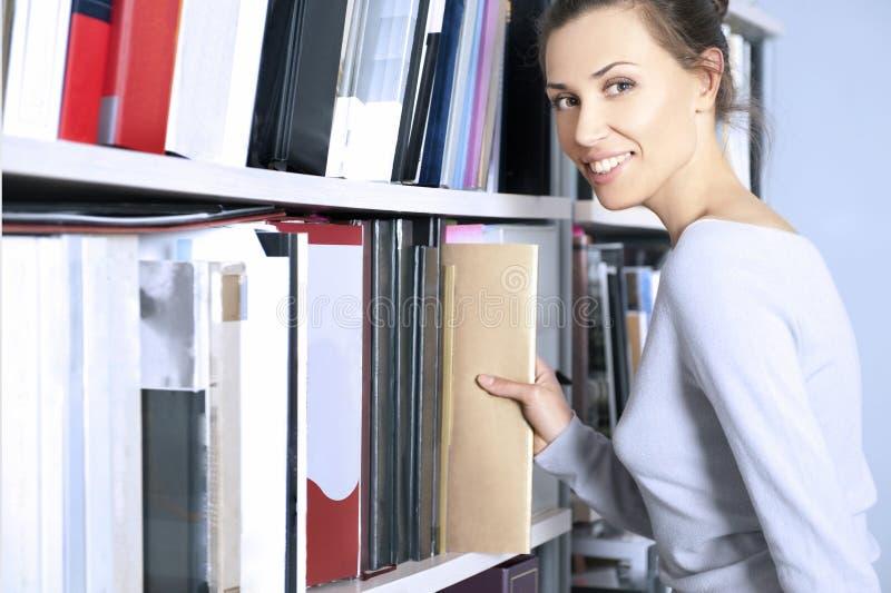półka na książki blisko młodych stojak kobiet zdjęcia stock