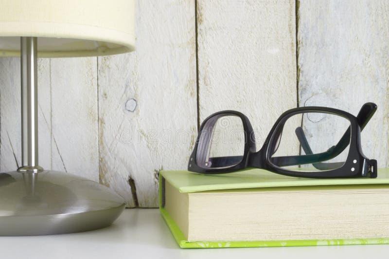 Półka z szkłami na książce i lampie przygotowywających dla czytelniczego czasu, obrazy stock