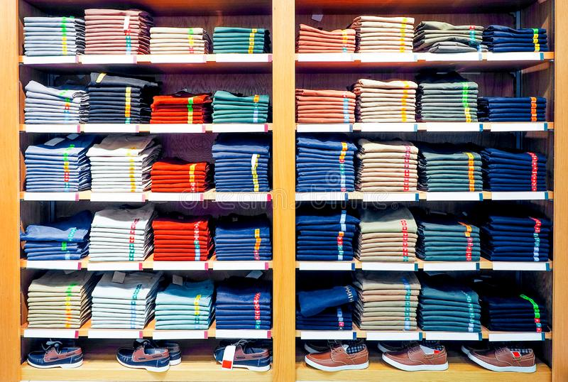 Półki z koszulkami i sneakers w wielkim sklepie odzieżowym zdjęcie stock