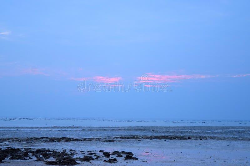 Półmrok przy Skalistą plażą czczość - pomarańcze kolory w niebieskim niebie - obraz royalty free