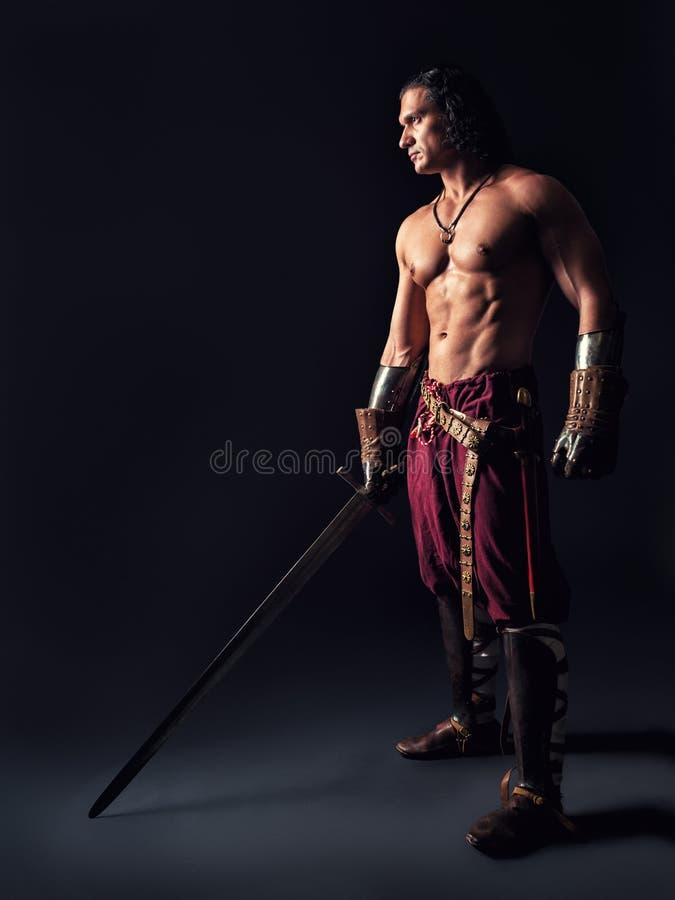 Półnagi wojownik z kordzikiem w średniowiecznym odziewa