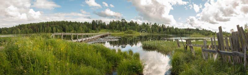 Północna Rosyjska wioska Isady Letni dzień, Emca rzeka, stare chałupy na brzeg, stary drewniany most i chmur odbicia, zdjęcia stock