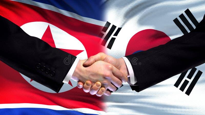 Północnego Korea i Południowego Korea uścisk dłoni, międzynarodowa przyjaźń, chorągwiany tło zdjęcia royalty free
