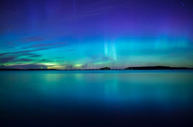 Północni światła tanczy nad spokojnymi jeziornymi zorz borealis zdjęcie stock