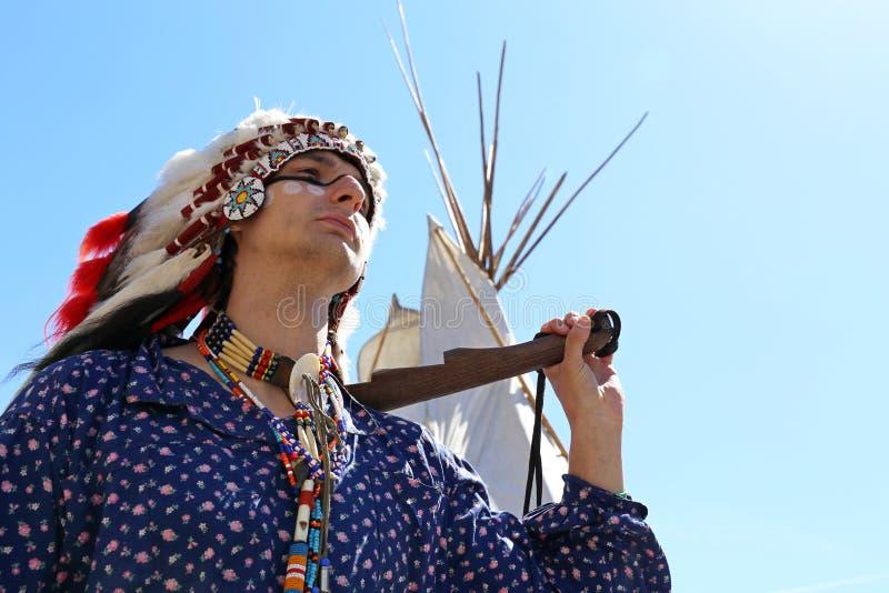Północnoamerykańscy indianów stojaki z bronią blisko wigwamu zdjęcia stock