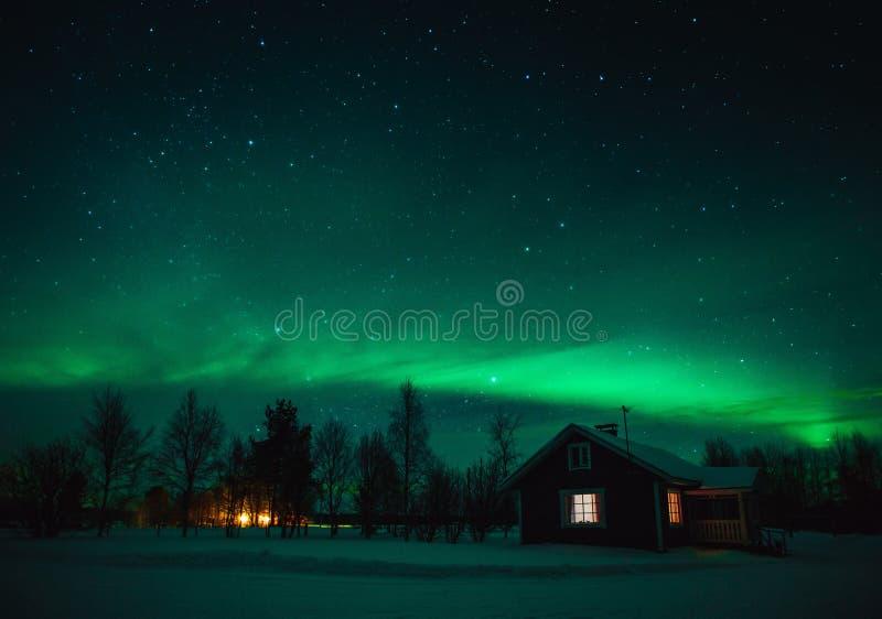 Północnych świateł zorza Borealis nad chałupą w Lapland wiosce Finlandia fotografia stock