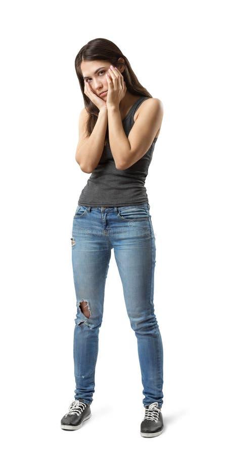 Półzwrotu widok młoda smutna kobieta stoi z rękami przy twarzą odizolowywającą na bielu w szarym sleeveless wierzchołku i niebies obrazy royalty free