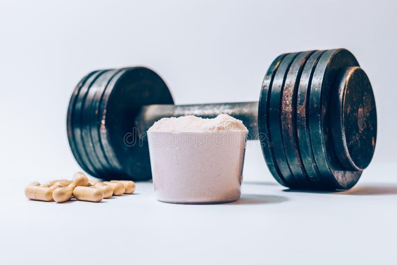 Pó da proteína do soro em uma colher ao lado do montão de comprimidos da vitamina foto de stock