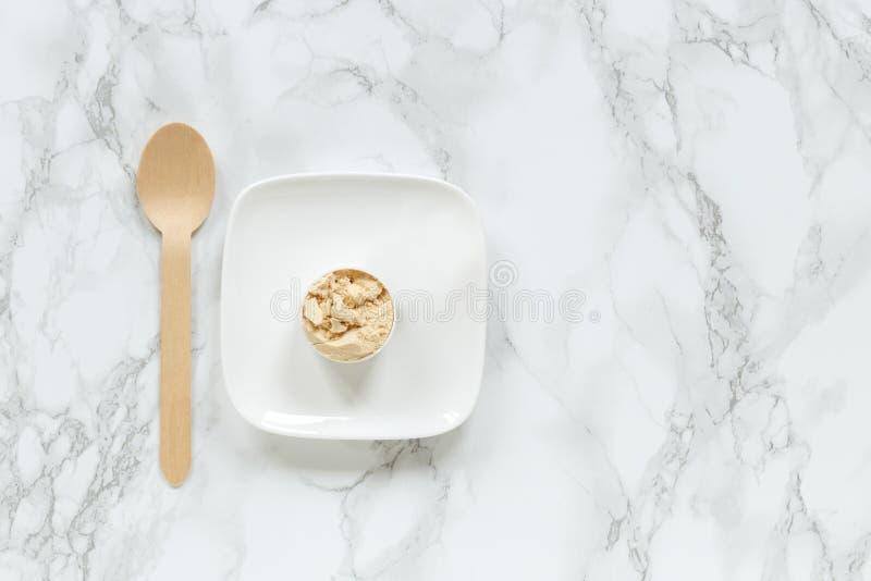 Pó da proteína na colher na placa pequena contra o fundo de mármore imagem de stock royalty free