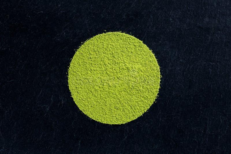 Pó do chá verde de Matcha no fundo preto da ardósia imagem de stock royalty free