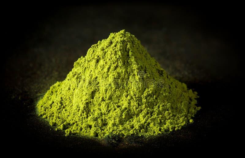 Pó do chá verde de Matcha no fundo preto do ferro fundido fotografia de stock