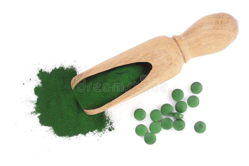 Pó e comprimidos de algas de Spirulina na colher de madeira isolada no fundo branco Vista superior fotografia de stock