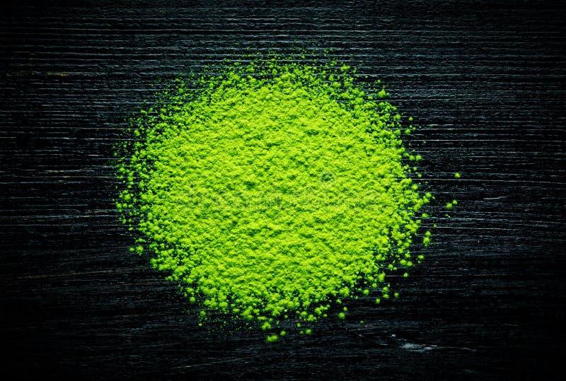 Pó verde do chá do matcha no fundo preto fotografia de stock royalty free