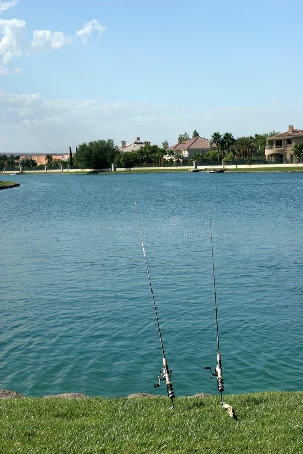 Pólos de pesca pela água foto de stock royalty free
