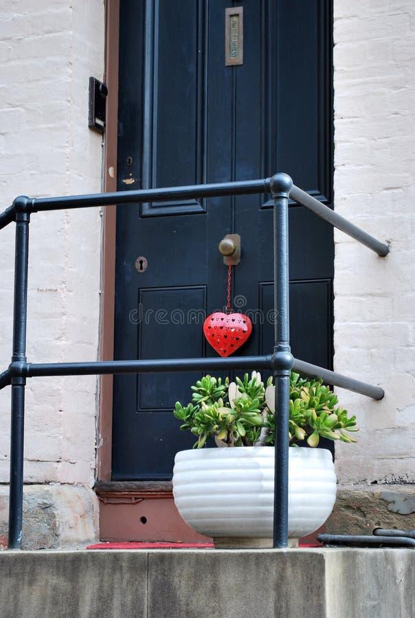 Pórtico adornado con una planta y un corazón en un botón de puerta fotos de archivo