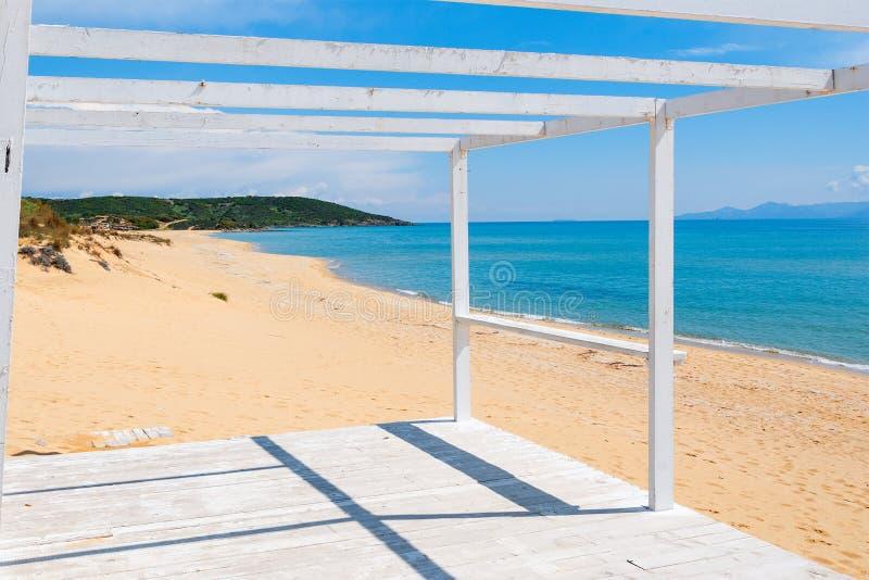 Pórtico de madera en una playa arenosa imagen de archivo