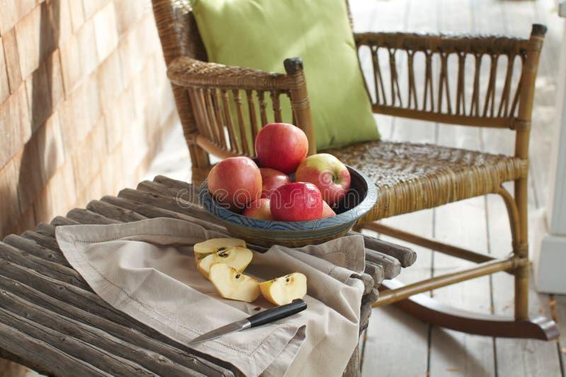 Pórtico rústico con las manzanas, silla de oscilación foto de archivo