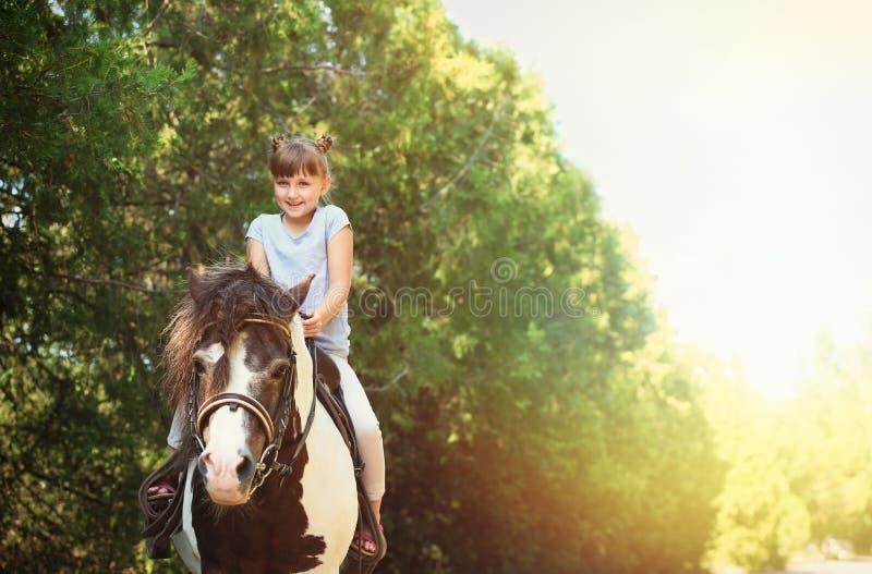 Pônei bonito da equitação da menina no dia ensolarado imagens de stock royalty free