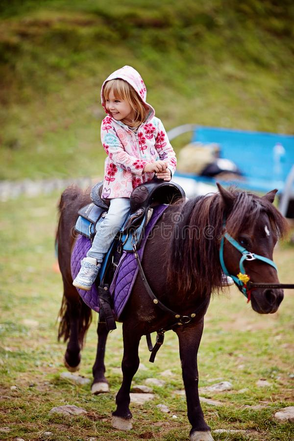 Pônei pequeno da equitação da menina imagens de stock
