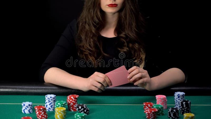 Pôquer perdedor redondo, mão má do gamer fêmea virado, microplaquetas do casino na tabela ao redor imagem de stock