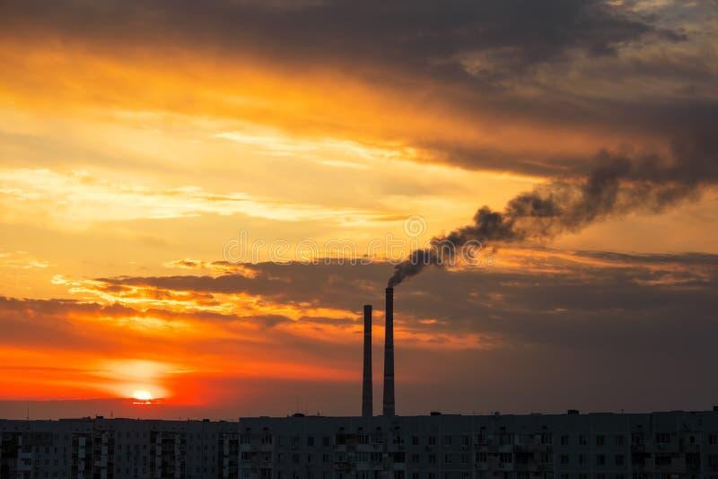 Pôr do sol mágico colorido Telhados de casas da cidade durante o amanhecer Fumaça escura proveniente do tubo da central térmica imagens de stock royalty free