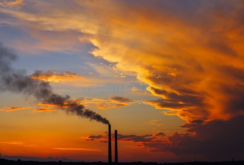 Pôr do sol mágico colorido Telhados de casas da cidade durante o amanhecer Fumaça escura proveniente do tubo da central térmica foto de stock royalty free