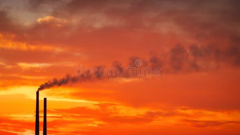 Pôr do sol mágico colorido Telhados de casas da cidade durante o amanhecer Fumaça escura proveniente do tubo da central térmica fotos de stock royalty free
