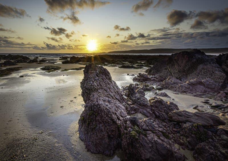 Pôr do sol na praia de rochas cênicas em Freshwater West, South Wales, UK imagem de stock royalty free