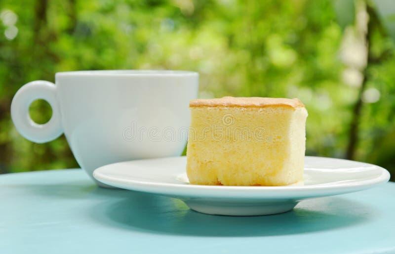 Põe manteiga a fatia do bolo para a parte no copo da placa e de café preto fotos de stock