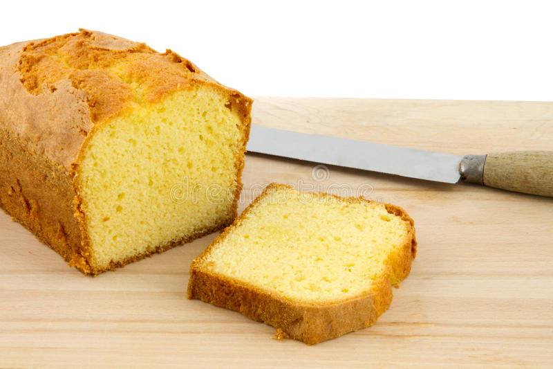 Põe manteiga o bolo e a fatia de bolo na placa de desbastamento fotografia de stock