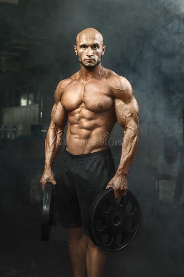 Põe muito o indivíduo atlético que está no gym com pesos e que lokking na câmera foto de stock royalty free
