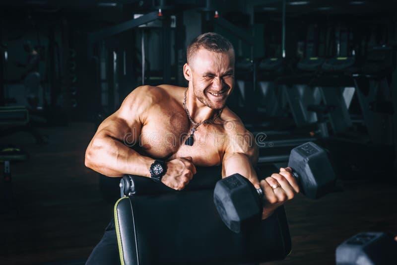 Põe o halterofilista atlético do indivíduo, execute o exercício com pesos, no gym escuro foto de stock