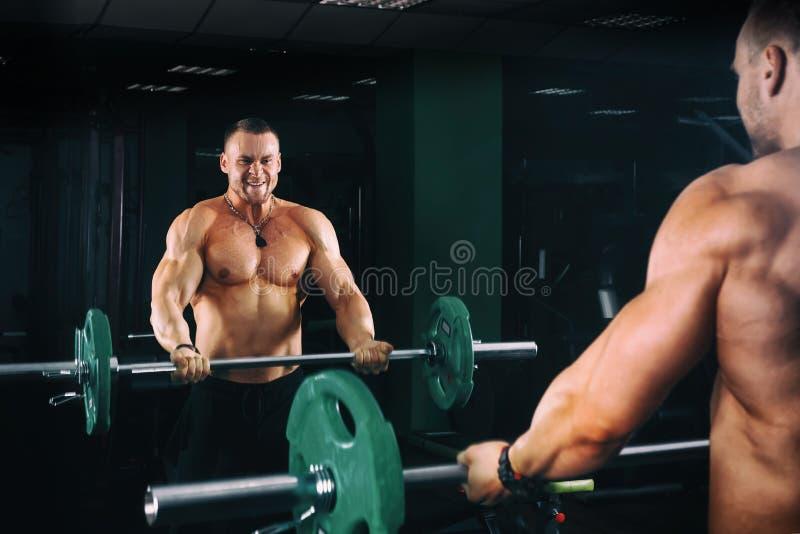 Põe o halterofilista atlético do indivíduo que dá certo o bíceps com o barbell na frente dos espelhos, no gym escuro foto de stock royalty free