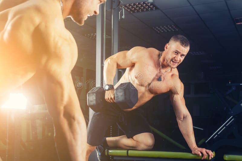 Põe o indivíduo atlético, execute a imprensa do exercício com pesos, no salão de esporte fotos de stock royalty free