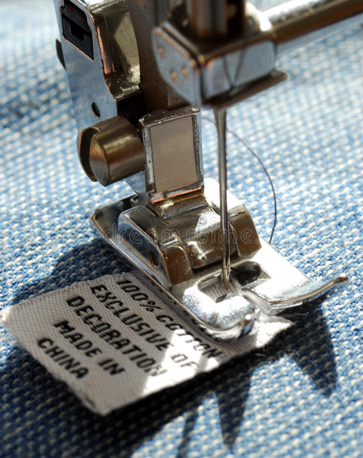 Põr a etiqueta do tamanho por uma máquina de costura imagem de stock