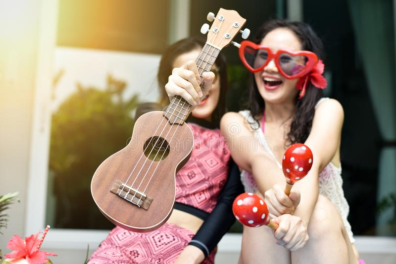Pölpartiet, lyckliga kvinnor tycker om att spela musikinstrumentet, genom simbassängen, flickvänner i bikinileende och att skratt royaltyfria bilder