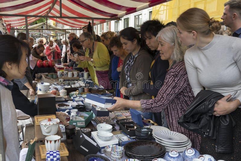 Público delante de un soporte para comprar cerámica japonesa en el mercado anual de Japón en Leiden fotos de archivo
