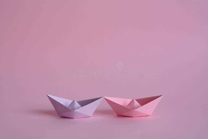 Púrpura y barcos de papel color de rosa en rosa en colores pastel fotos de archivo