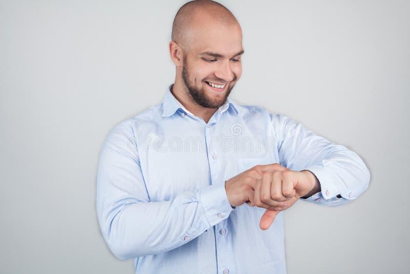 Pünktliche Mannpunkte am Handgelenk, seiend sehr emotional, trägt weißes Hemd Hübsche Kerlkontrollzeit, lokalisiert über weißem H stockfotos