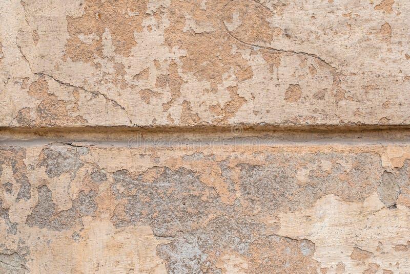 Pęknięcia w starej tynk ścianie, odłupana farba, beżowa tekstura, tło obrazy stock