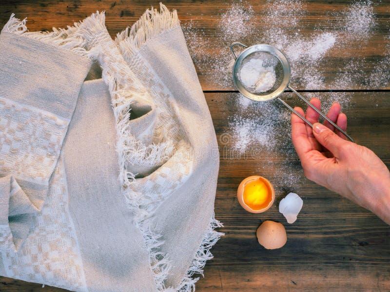 Płótno od szorstkiej tkaniny na tle stary drzewo i rozrzucona mąka Kobiety ` s ręka odsiewa mąkę Skład wewnątrz zdjęcia royalty free