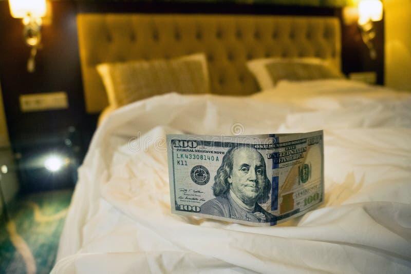 płacić pieniądze dolara na białym łóżku w hotelu obrazy royalty free