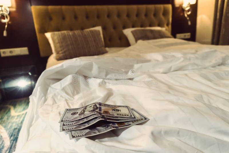 płacić pieniądze dolara na białym łóżku w hotelu zdjęcia royalty free