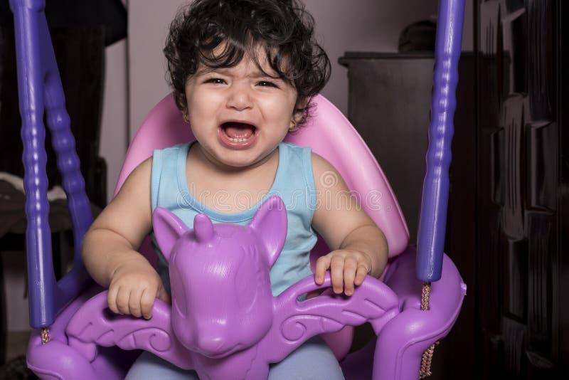 Płaczący małej dziewczynki na jednorożec huśtawce, wyposażającej w domu dla k zdjęcie stock