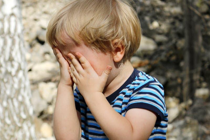 Płacz chłopiec, chłopiec bawić się kryjówkę aport - i - zdjęcie royalty free