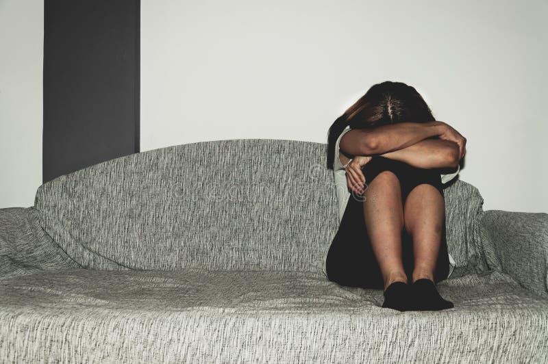 Płacz kobieta nadużywająca jako młody uczucie deprymujący i nędzny podczas gdy ona siedzi samotnie w jej pokoju zdjęcia stock