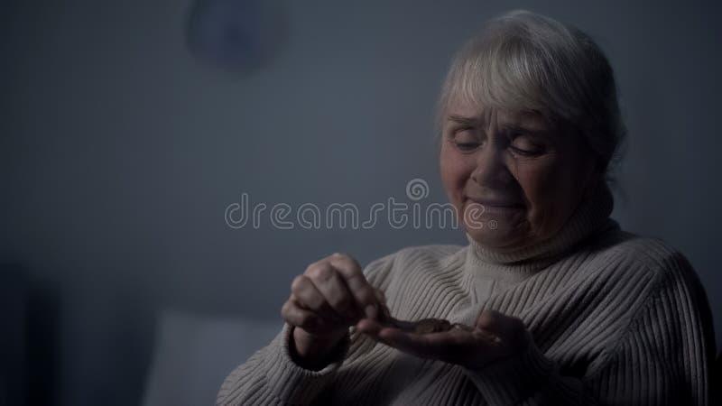 P?aka? starsze kobiety liczenia monety w r?ce, og?lnospo?eczna niepewno??, emerytalny ub?stwo zdjęcie stock
