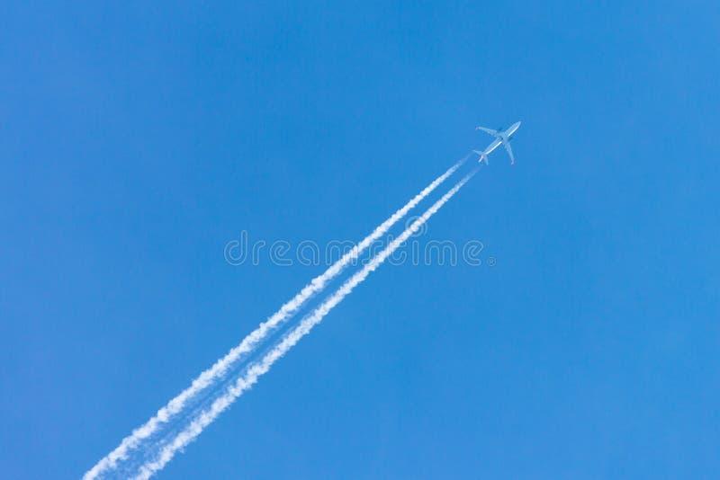 Płaska latająca wysokość w jasnym niebieskim niebie opuszcza długiego białego ślad obraz stock