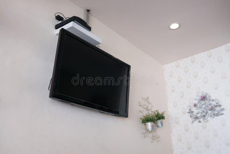 Płaski ekran tv lcd na ścianie z wystroju kwiatem obrazy royalty free