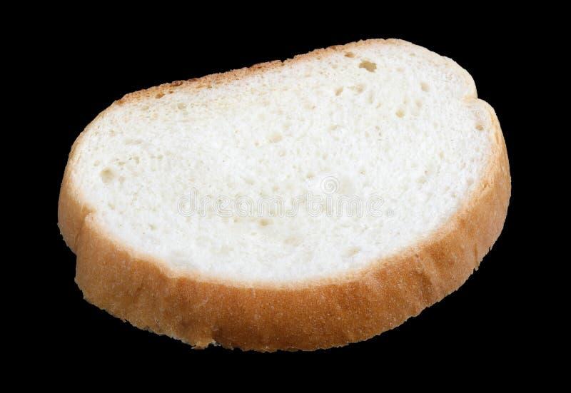 Płaski kawałek biały pszeniczny chlebowy kłamstwo na stole odizolowywającym na czarny makro- fotografia stock